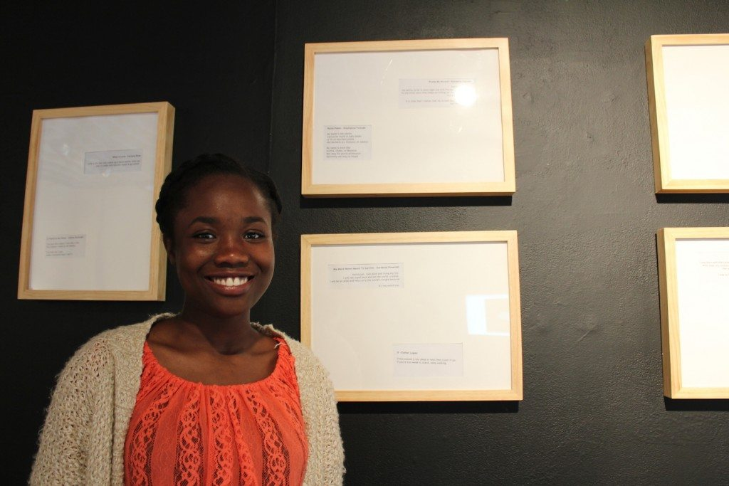"Kimberly Cajuste standing next to her poem ""Praise my Accent."""